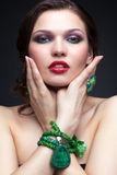 Beautiful young woman in necklace. Portrait of beautiful young brunette woman in malachite necklace  touching her face on dark gray background Royalty Free Stock Image