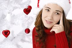 Beautiful young woman next to christmas tree Royalty Free Stock Photo