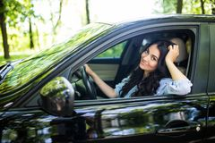 Beautiful young woman in the nice car looks happy and relaxed is going to vacation. stock photo