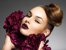 Beautiful young woman with a nice hairstyle and flowers. royalty free stock photography
