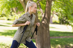 Beautiful young woman Nordic walking in park Stock Images