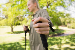 Beautiful young woman Nordic walking in park Royalty Free Stock Images