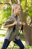Beautiful young woman Nordic walking in park Stock Photos
