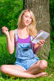 Beautiful young woman with note pad. Sitting on the lawn Stock Photo