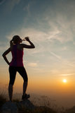 Beautiful young woman observing sunset with bottle of water Stock Photo