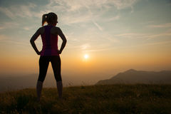 Beautiful young woman observing sunset after running on a mountian Royalty Free Stock Photography