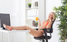Beautiful young woman at office in bikini dreams Stock Photo