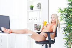 Beautiful young woman at office in bikini dreams Royalty Free Stock Photos