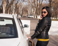 Young woman with cellphone. Beautiful young woman opened the car door and talking on the cellphone Royalty Free Stock Images
