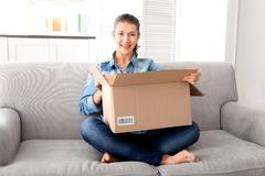 Beautiful young woman opening box with parcel. While sitting on sofa at home stock photos