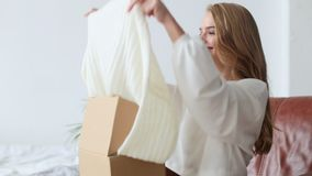 Beautiful young woman opening box with parcel at home stock video
