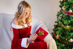 Beautiful young woman opening christmas gift Royalty Free Stock Photos