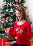Beautiful young woman opening a Christmas present Stock Images