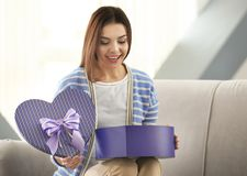 Beautiful young woman opening gift box. At home Royalty Free Stock Photography