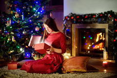 Beautiful young woman opening magical Christmas gift by a fireplace Royalty Free Stock Images