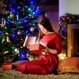 Beautiful young woman opening magical Christmas gift by a fireplace Royalty Free Stock Photo