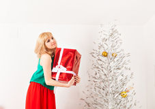 Beautiful young woman opening present box near a Stock Photo