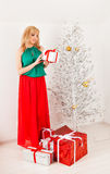 Beautiful young woman opening present box near a Stock Images
