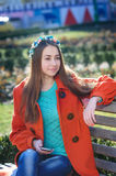 Beautiful young woman in orange coat sitting on the bench with a phone Stock Images