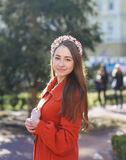 Beautiful young woman in orange coat walking in the city Royalty Free Stock Photos
