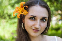 Beautiful young woman with an orange lily Royalty Free Stock Photos