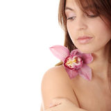 Beautiful young woman with orchid. Studio portrait of beautiful young woman with orchid and professional makeup Stock Images