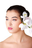 Beautiful young woman with orchid flower Royalty Free Stock Photography