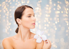Beautiful young woman with orchid flower. Beauty, people, bodycare and health concept - beautiful young woman with orchid flower and bare shoulders over holidays Stock Images