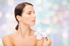 Beautiful young woman with orchid flower. Beauty, people, bodycare and health concept - beautiful young woman with orchid flower and bare shoulders over holidays Stock Photos