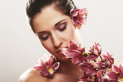 Beautiful young woman with orchid flowers Royalty Free Stock Image
