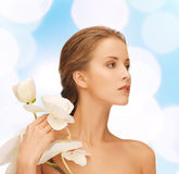 Beautiful young woman with orchid flowers. Beauty, people and health concept - beautiful young woman with orchid flowers and bare shoulders over blue lights Royalty Free Stock Photo