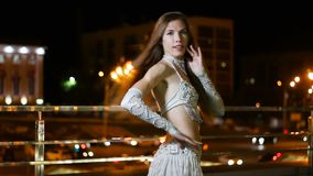 Beautiful young woman in oriental ethnic costume dances at night outdoor.  stock video footage