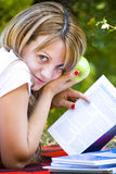 Beautiful young woman outdoor. Beautiful young woman with books and holding apple Royalty Free Stock Photos
