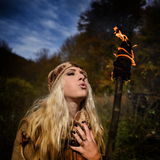 Beautiful young woman outdoor on autumn day holding burning torc Royalty Free Stock Images