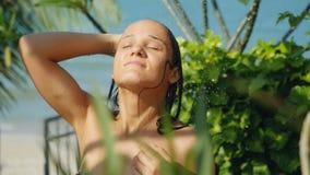 Beautiful young woman in outdoor shower. Sensual and Seductive has a washing enjoys splashing water on summer holidays. Beautiful young woman in outdoor shower Stock Photo