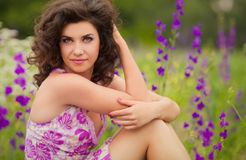 Beautiful young woman outdoors. Beautiful young woman in purple flowers outdoors Stock Photography