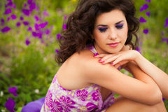 Beautiful young woman outdoors. Beautiful young woman in purple flowers outdoors Stock Image