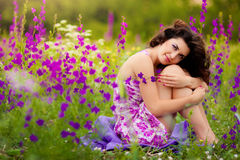 Beautiful young woman outdoors. Beautiful young woman in purple flowers outdoors Stock Photo