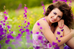 Beautiful young woman outdoors. Beautiful young woman in purple flowers outdoors Stock Images