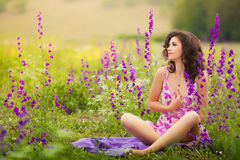 Beautiful young woman outdoors. Beautiful young woman in purple flowers outdoors Stock Photos