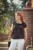 Beautiful young woman outdoors. Cute Red-haired girl in summer Royalty Free Stock Photo