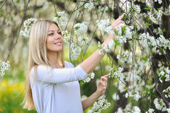Beautiful young woman outdoors. Enjoy nature in blooming trees i Stock Photo