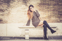 Beautiful young woman outdoors sitting on a bench. Fashionable and sensual Royalty Free Stock Photography