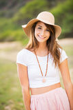 Beautiful young woman outdoors in sun hat. Stock Photography