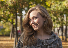 Beautiful young woman outside in autumn city park Royalty Free Stock Photo