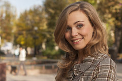 Beautiful young woman outside in autumn city park Stock Photo
