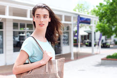 Beautiful young woman outside of building with purse Royalty Free Stock Image