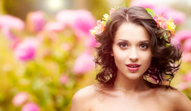 Beautiful young woman over autumn background. Beautiful young woman with flowers in hair over autumn background Stock Images
