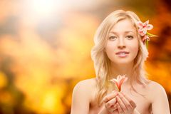Beautiful young woman over autumn background. Beautiful young woman holding flower over autumn background Stock Photos