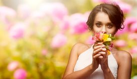 Beautiful young woman over autumn background. Beautiful young woman holding flowers over autumn background Stock Photo